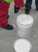 Firestone Water Based Adhesive being stirred ready for use.